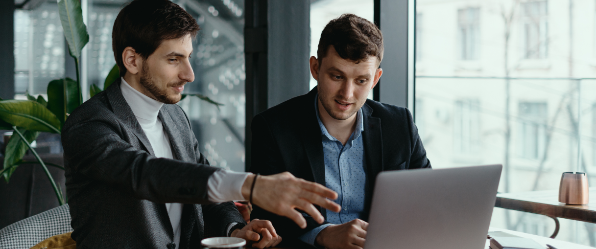 two-businessmen-pointing-laptop-screen-while-discussing 2